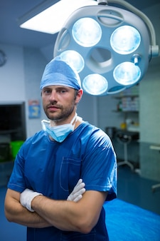 Ritratto del chirurgo in piedi con le braccia incrociate in sala operatoria