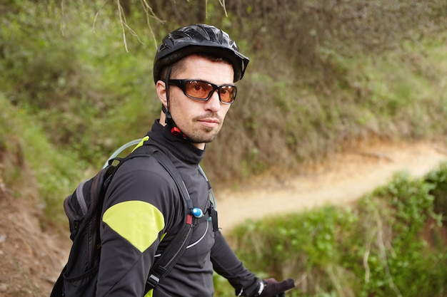 Ritratto del ciclista professionista fiducioso bello in abbigliamento sportivo, occhiali, casco e zaino