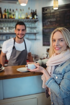 Ritratto del cliente femminile con il barista al caffè