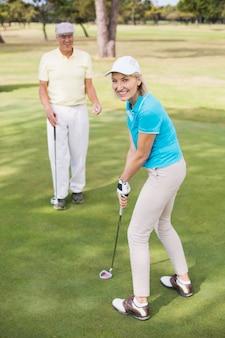 Ritratto del club di golf della tenuta della donna dall'uomo
