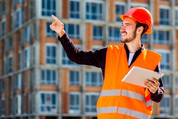 Ritratto del colpo medio dell'architetto sorridente che indica via