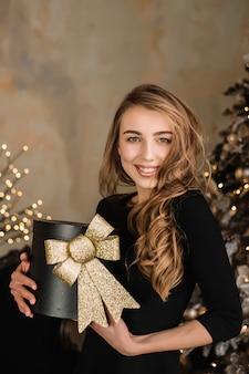 Ritratto del contenitore di regalo grazioso della holding della ragazza in mani. natale