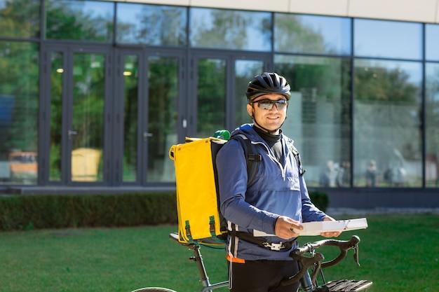 Ritratto del corriere della bicicletta con la borsa e la bici gialle