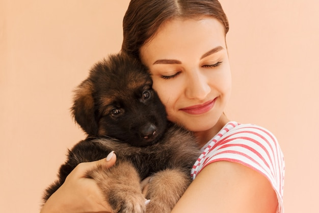 Ritratto del cucciolo di pastore tedesco in posa sulle mani della donna