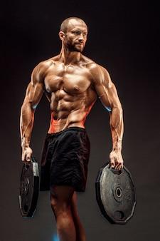 Ritratto del culturista con le teste di legno in sue braccia su backg grigio