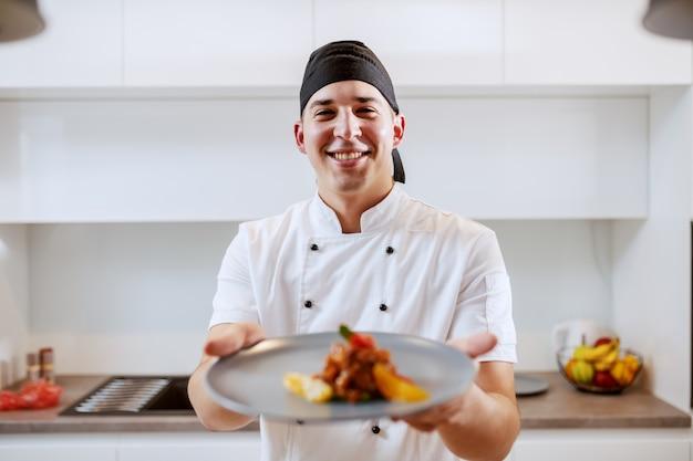Ritratto del cuoco unico caucasico in uniforme che tiene piatto con salmone e frutta arancione.