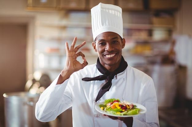 Ritratto del cuoco unico felice che fa segno giusto