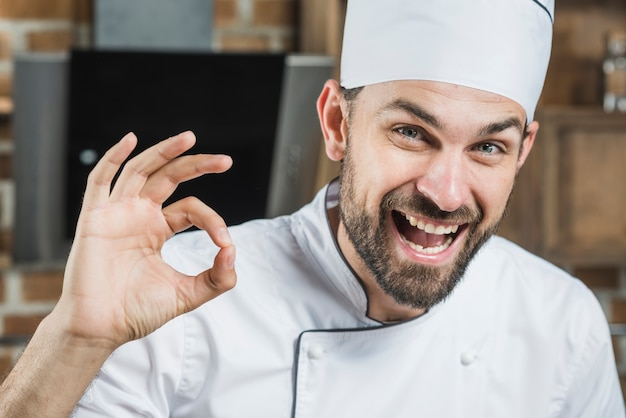 Ritratto del cuoco unico maschio sorridente che mostra segno giusto