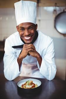 Ritratto del cuoco unico sorridente che presenta insalata