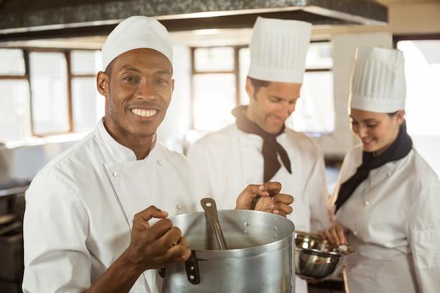 Ritratto del cuoco unico sorridente che tiene un vaso di cottura