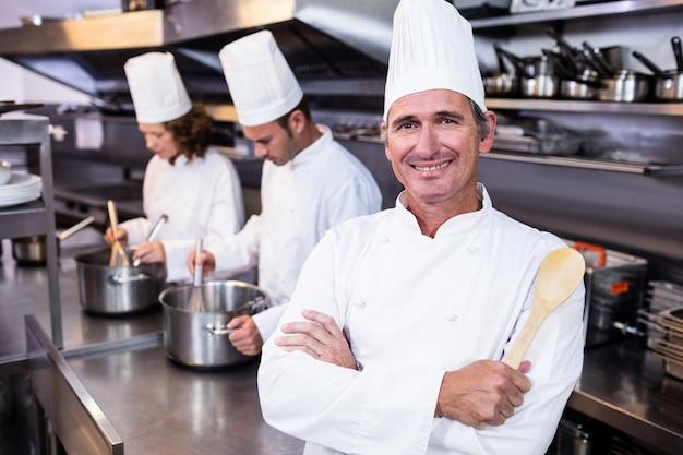 Ritratto del cuoco unico sorridente in cucina commerciale