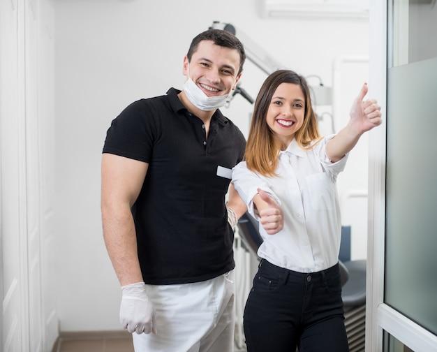 Ritratto del dentista maschio amichevole con il paziente femminile felice dopo il trattamento in studio dentistico moderno.