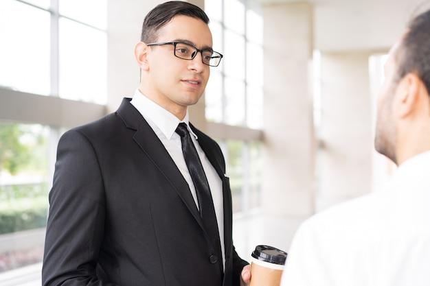 Ritratto del dirigente serio in vetri che ascolta l'impiegato