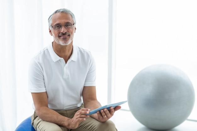 Ritratto del fisioterapista che si siede nella palla di esercizio e che utilizza compressa digitale a casa