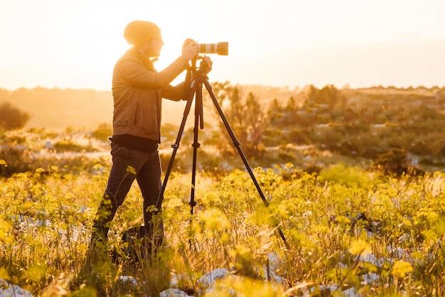 Ritratto del fotografo che fa le foto con la macchina fotografica sul treppiede al tramonto