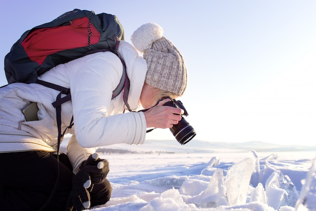 Ritratto del fotografo femminile che spara al paesaggio invernale accanto al lago baikal congelato. turismo invernale in russia