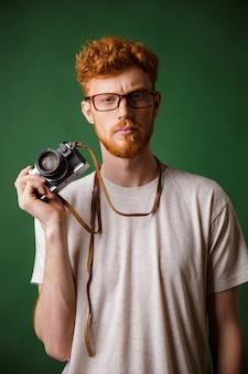 Ritratto del fotografo serio dei pantaloni a vita bassa del readhead con la macchina fotografica