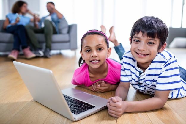 Ritratto del fratello che per mezzo della menzogne sul pavimento e per mezzo del computer portatile