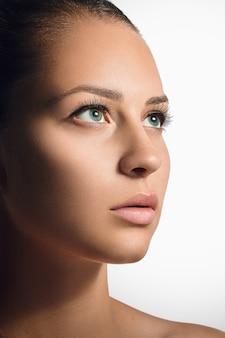 Ritratto del fronte di bellezza della donna isolato su bianco con pelle sana
