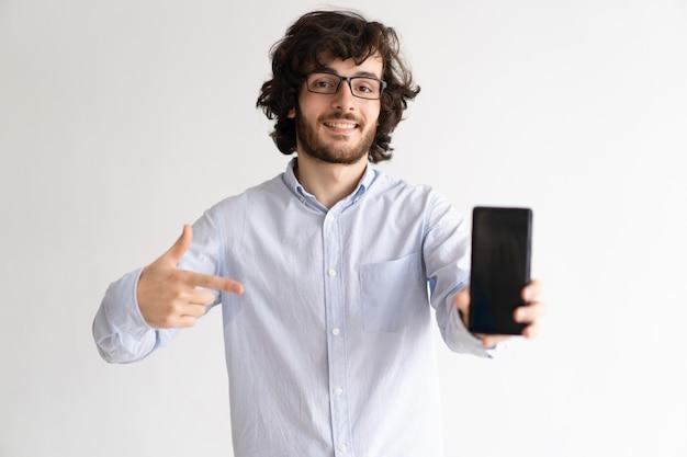 Ritratto del gestore allegro in vetri che fanno pubblicità allo smartphone.