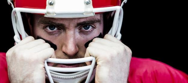 Ritratto del giocatore di football americano che tiene sul suo casco
