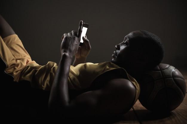 Ritratto del giocatore di pallacanestro che si trova e che per mezzo del suo smartphone