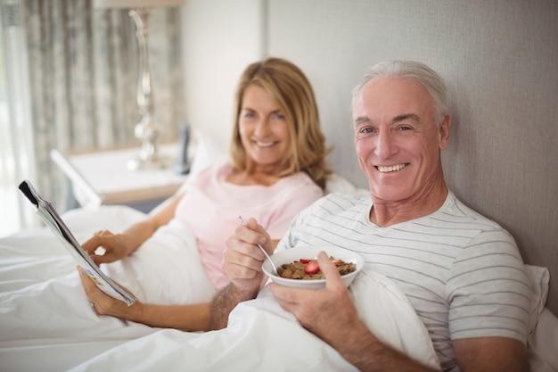 Ritratto del giornale sorridente della lettura delle coppie mentre mangiando prima colazione