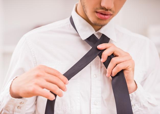 Ritratto del giovane alla moda bello che indossa una cravatta.