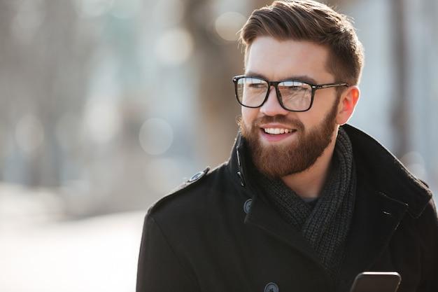 Ritratto del giovane barbuto felice in vetri che stanno all'aperto