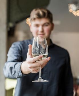 Ritratto del giovane bello che tiene un drink