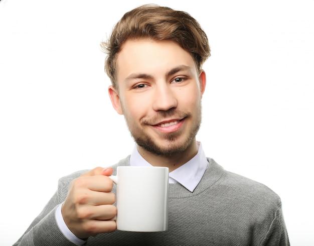 Ritratto del giovane bello con la tazza, isolato su bianco.