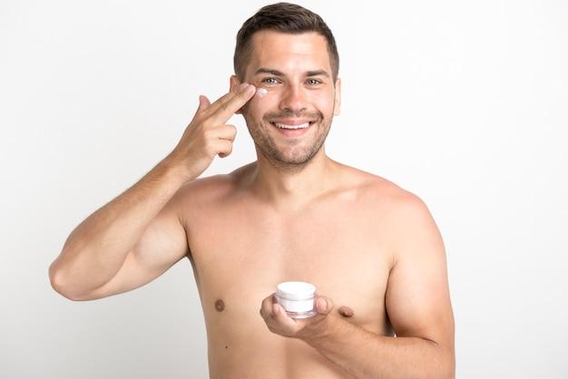 Ritratto del giovane che applica la crema di fronte sul fronte che sta contro il fondo bianco