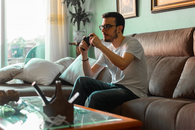 Ritratto del giovane che gioca video gioco che tiene regolatore senza fili nella sua casa.