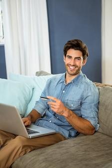 Ritratto del giovane che si siede sul sofà e che compera online sul computer portatile