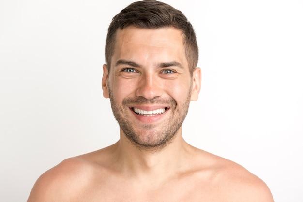 Ritratto del giovane che sorride e che esamina macchina fotografica che sta contro il fondo bianco