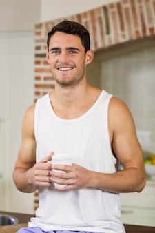 Ritratto del giovane che sorride e che tiene una tazza di tè in cucina