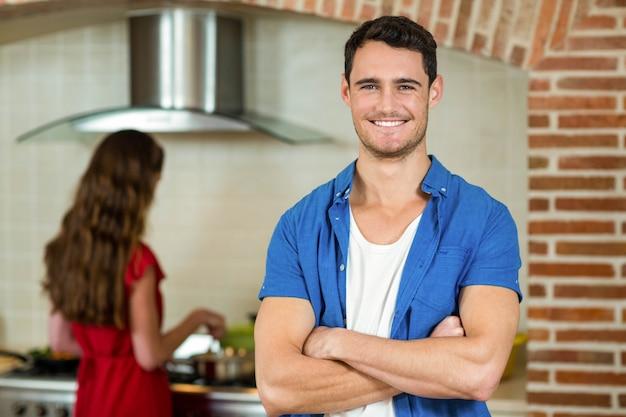 Ritratto del giovane che sorride nella cucina mentre donna che cucina sulla stufa