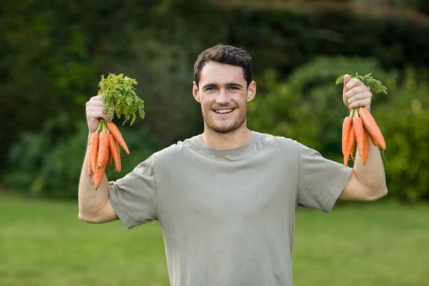 Ritratto del giovane che tiene mazzo di carote appena colte in entrambe le mani