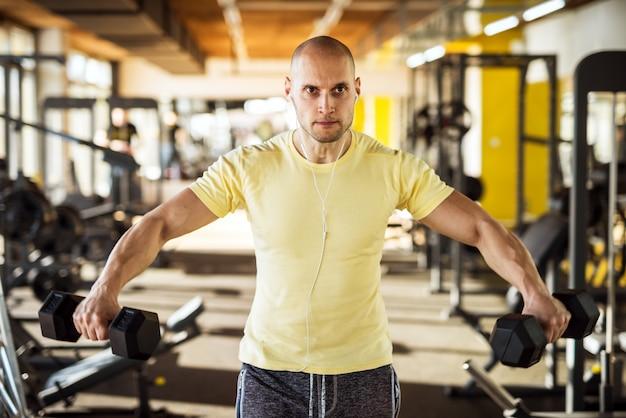 Ritratto del giovane in buona salute attivo muscolare forte che alza le teste di legno con a braccia aperte e musica d'ascolto in palestra.