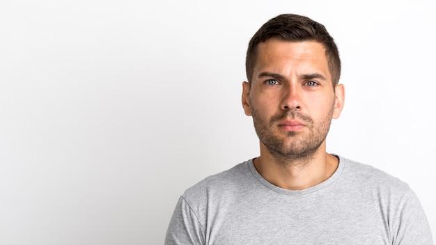 Ritratto del giovane in maglietta grigia che esamina macchina fotografica che sta contro la parete bianca