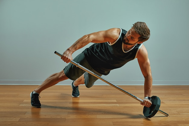 Ritratto del giovane muscolare di misura eccellente che risolve in palestra con il bilanciere su fondo grigio, copyspace.