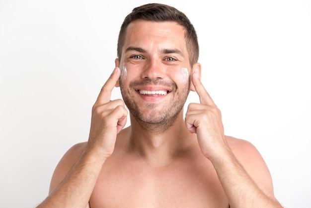 Ritratto del giovane senza camicia che massaggia con la crema contro il fondo bianco