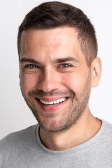 Ritratto del giovane sorridente in maglietta grigia che esamina macchina fotografica