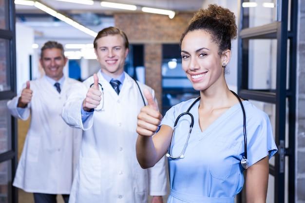 Ritratto del gruppo di medici che mette i loro pollici su e sorridere