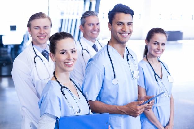 Ritratto del gruppo di medici che sta insieme e che sorride nell'ospedale