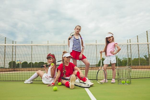 Ritratto del gruppo di ragazze come tennis che tengono la racchetta di tennis contro l'erba verde della corte all'aperto