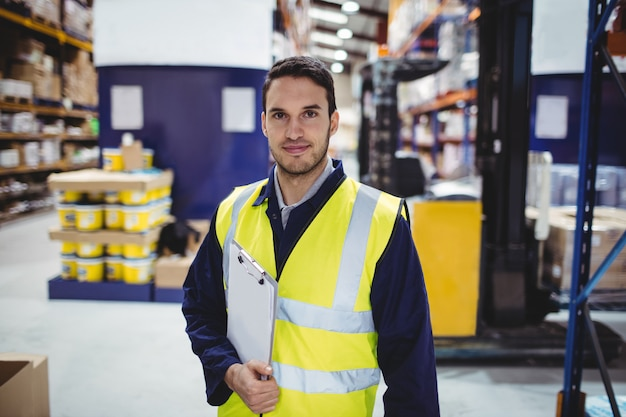 Ritratto del lavoratore del magazzino con la lavagna per appunti in magazzino
