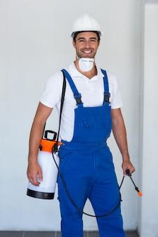 Ritratto del lavoratore manuale felice con insetticida