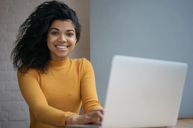 Ritratto del libero professionista del copywriter che per mezzo del computer portatile, funzionante dalla casa. studente che impara la lingua online