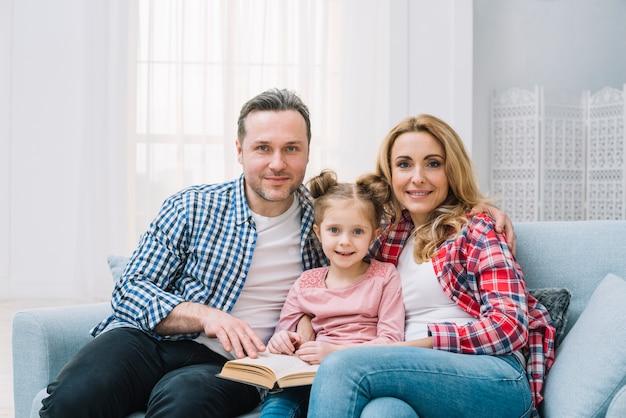 Ritratto del libro di lettura della famiglia che si siede insieme sul sofà